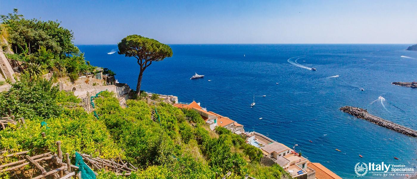 View of trees and houses of the town of Amalfi, Italy, by the sea