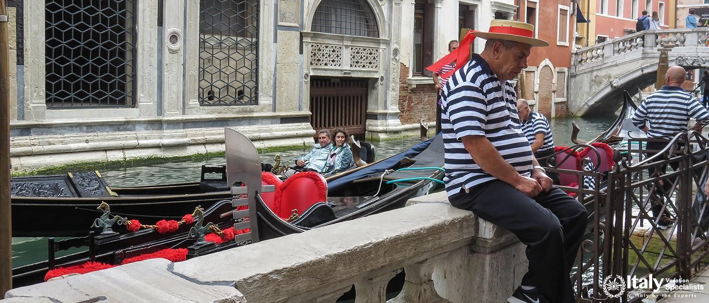 ITALY, VENICE - OCTOBER 15, 2014Typical Venetian gondolier in traditional clothing is waiting for cu