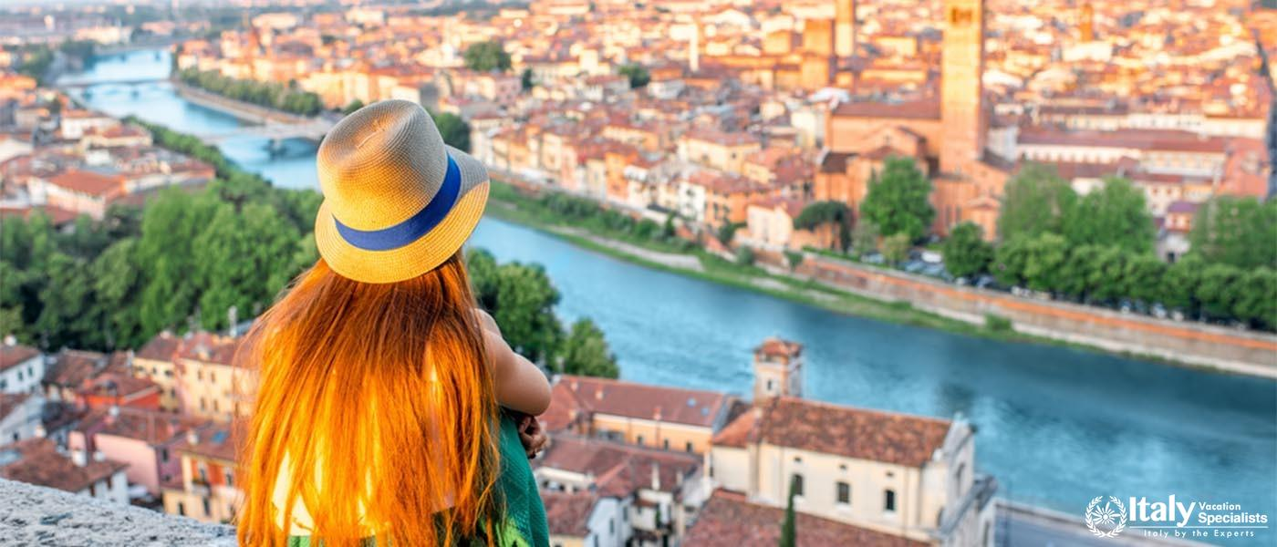Woman enjoying beautiful view on Verona city in Italy on the sunrise. Verona is famous city of love